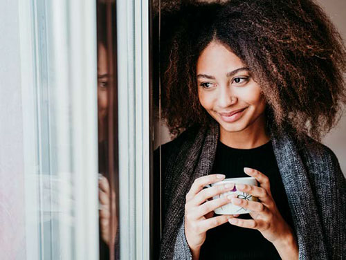 a woman holding a cup of coffee and smiling