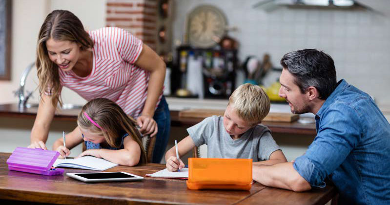 mother and father helping children with homework at kitchen table