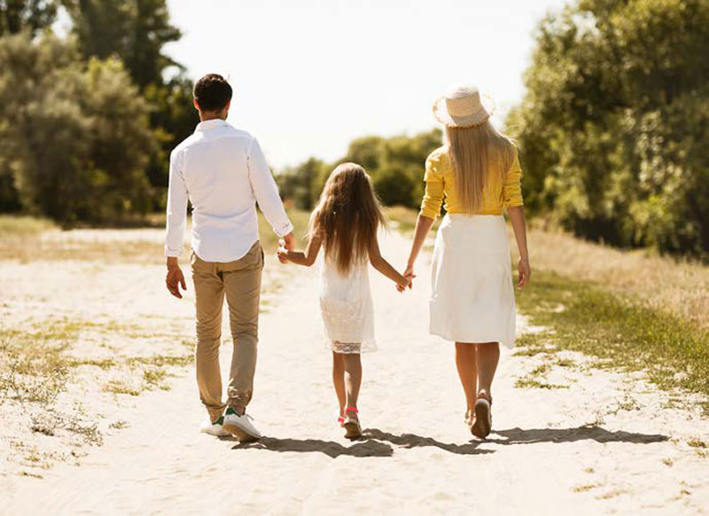 couple walking hand-in-hand with their daughter