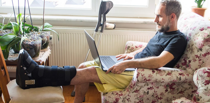 man sitting on couch with a broken leg using a laptop computer