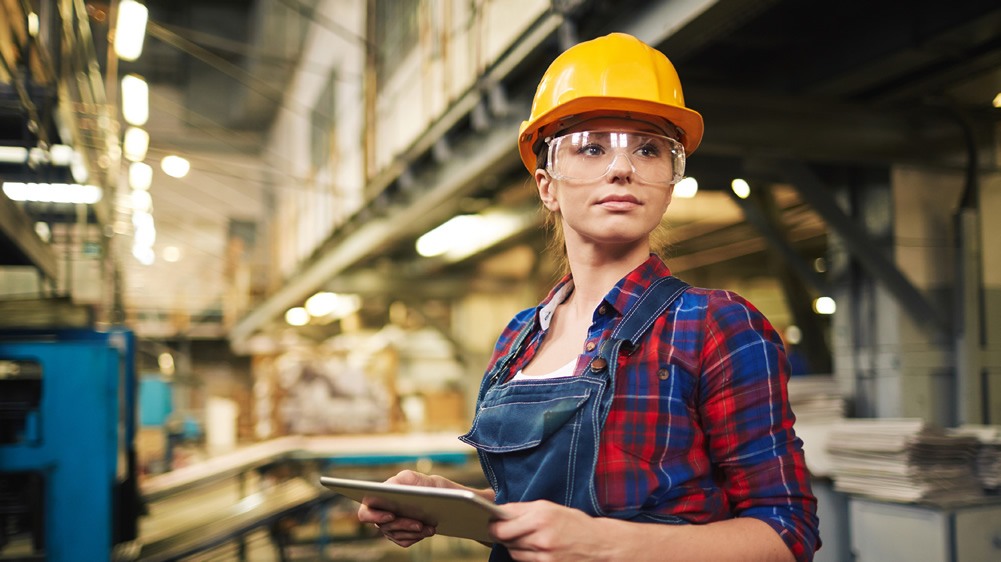 woman in manufacturing/industrial setting, wearing hard-hat and safety glasses
