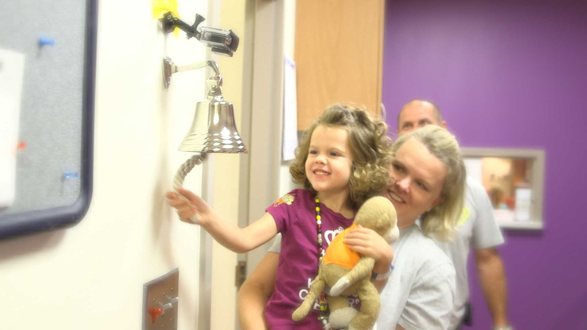 little girl ringing the 'end of treatment bell'