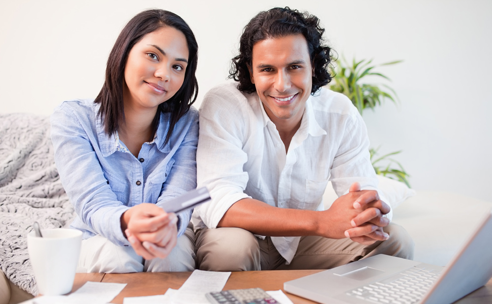 woman and man sitting on couch, shopping online / paying bills