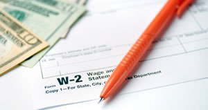 money and pen laying on IRS W-2 form