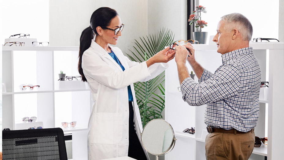 an eye doctor handing a patient a pair of glasses