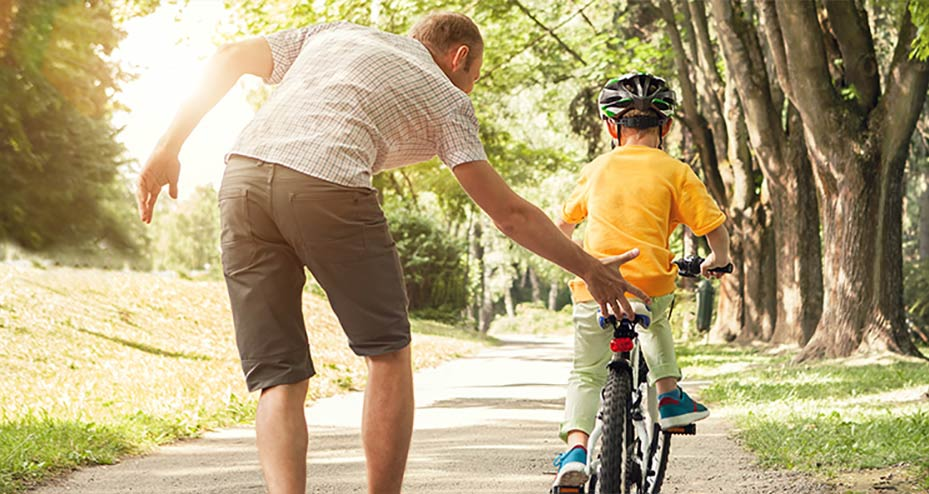 Father helping his son learn how to ride a bicycle