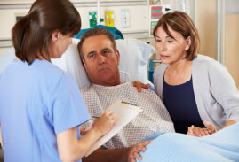 man in hospital bed, woman by his side, having discussion with doctor/nurse