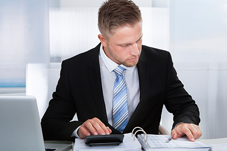 Businessman working at desk with calculator going over books