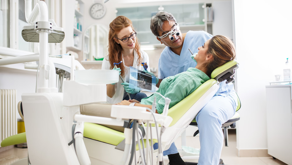 dentist and dental assistant with patient in chair