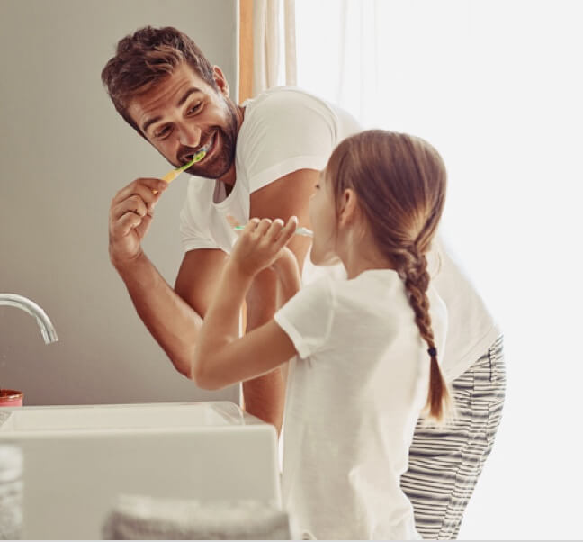 A father brushing teeth with a daughter